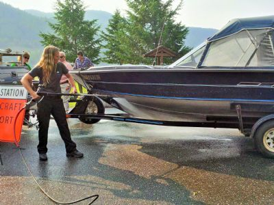 Ember Heidt, Compliance and Enforcement Officer with the Conservation Officer Service demonstrates how to decontaminate a boat with suspected invasive mussels.